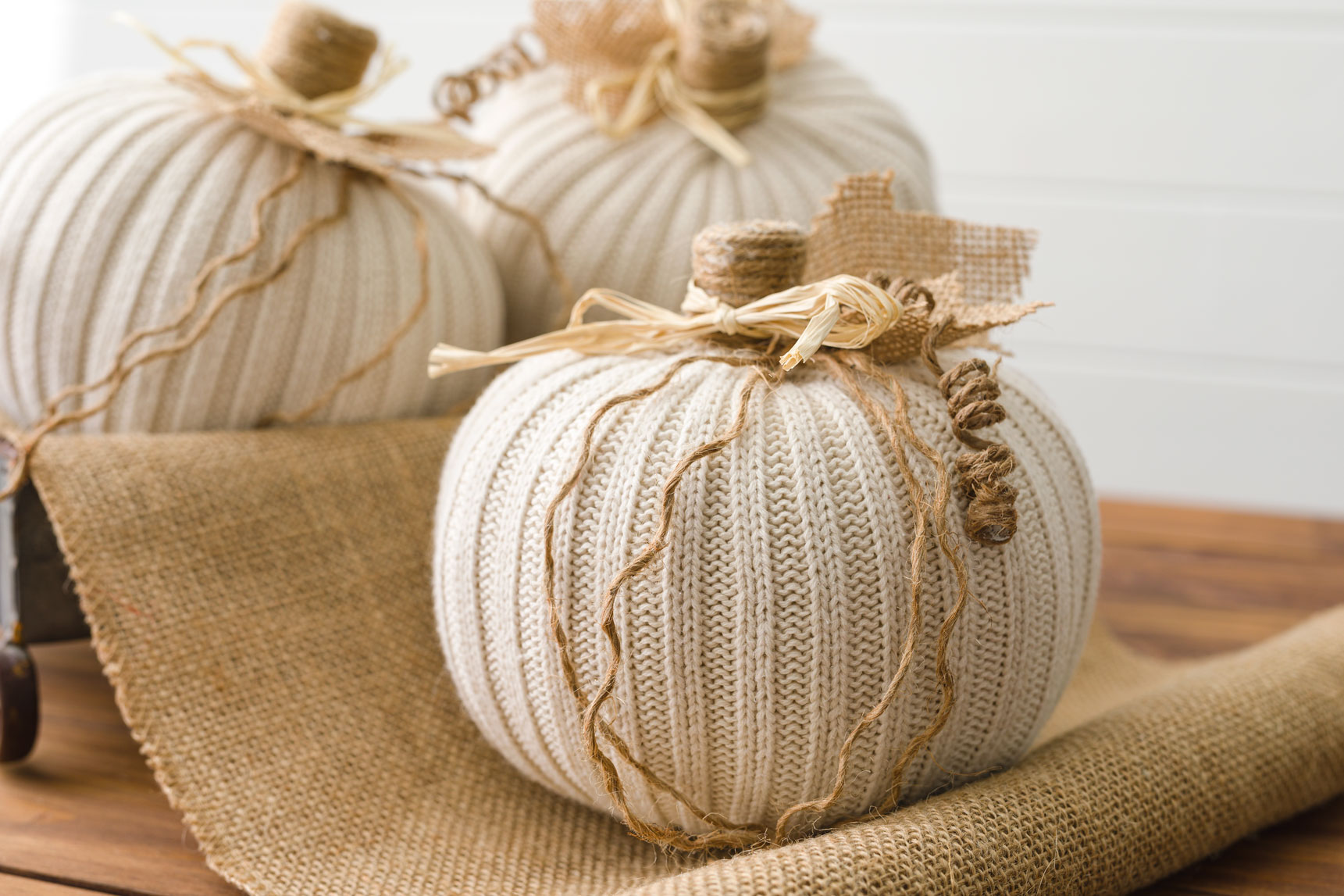 Cream sweater pumpkins on a table with burlap