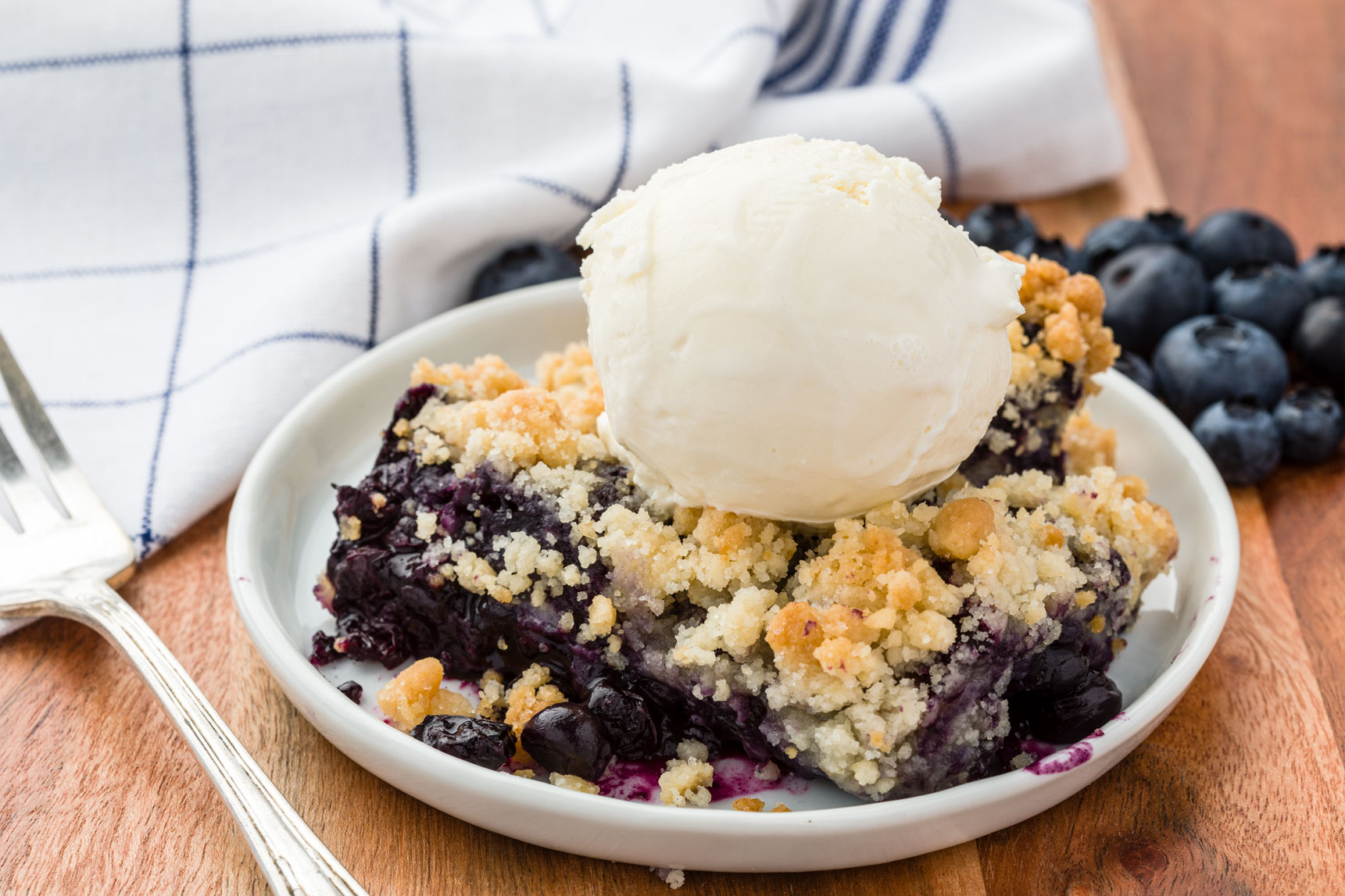 Blueberry crisp topped with vanilla ice cream on a small plate
