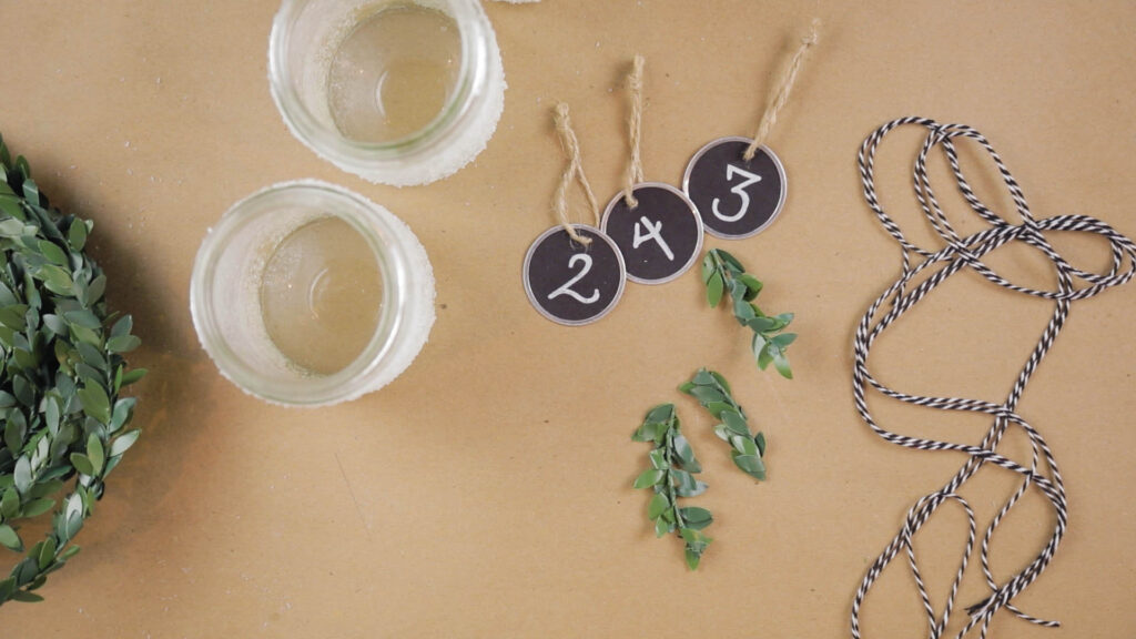 Jars, number tags, bakers twine and green leaves on the brown piece of paper