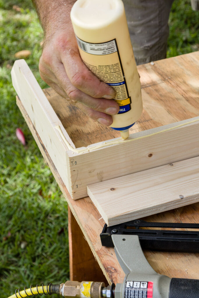 Applying wood glue to the face of the shoe rack