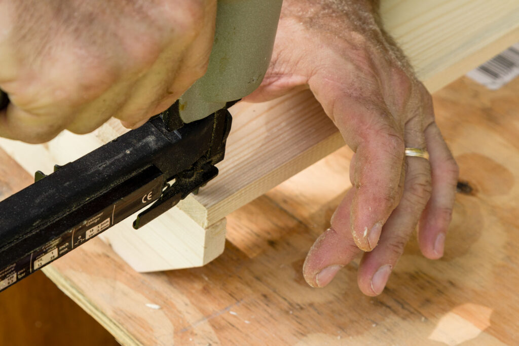 Adding the top back board to the shoe rack using a stapler