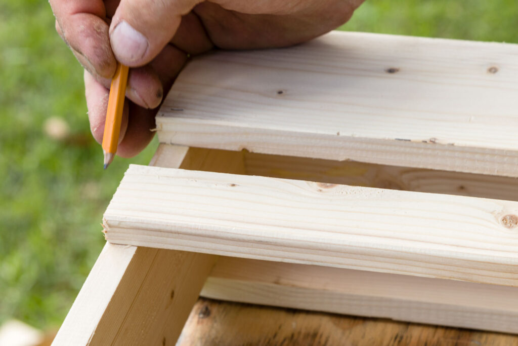 Marking the upper front board location with a pencil on the shoe rack