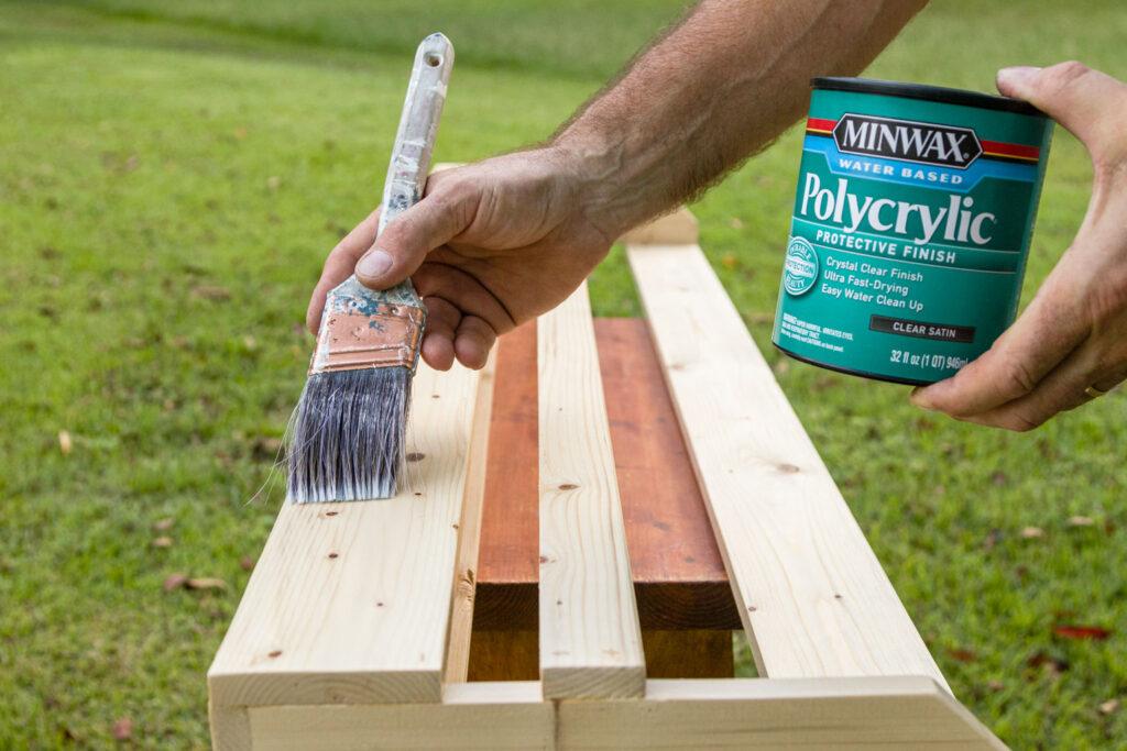 Brushing on polycrylic on the sanded wood racks