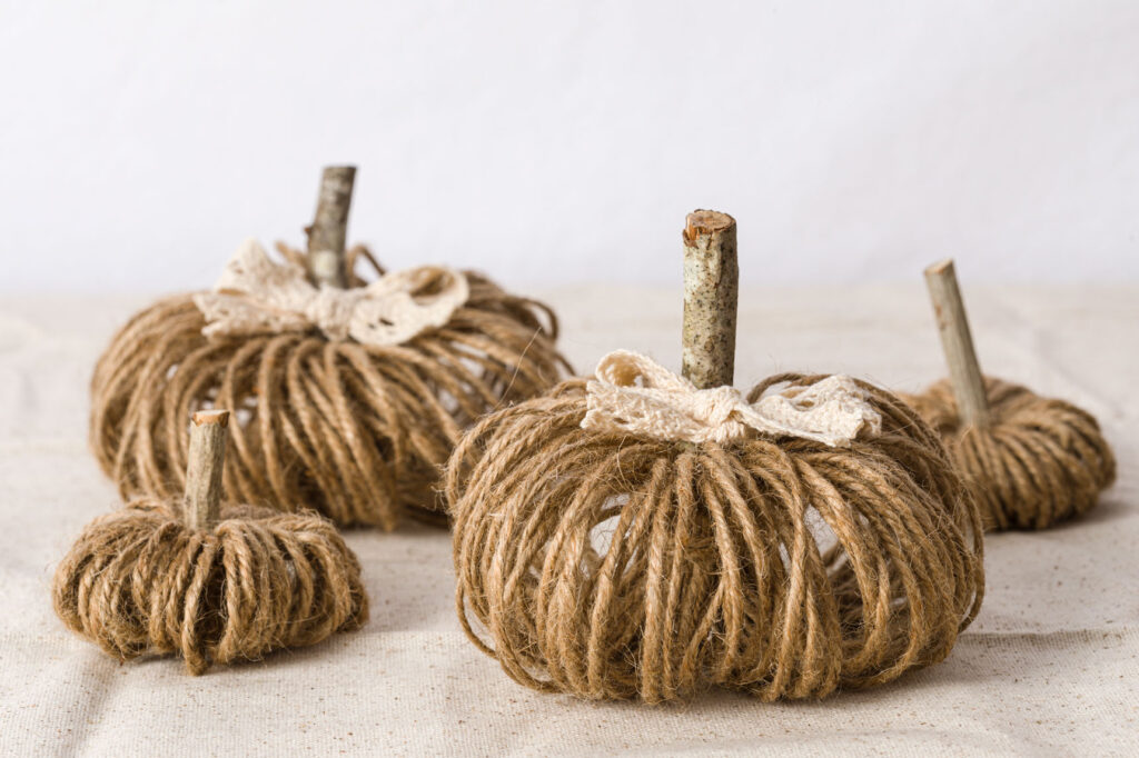 Twine Pumpkins DIY sitting on a table with cotton lace ties