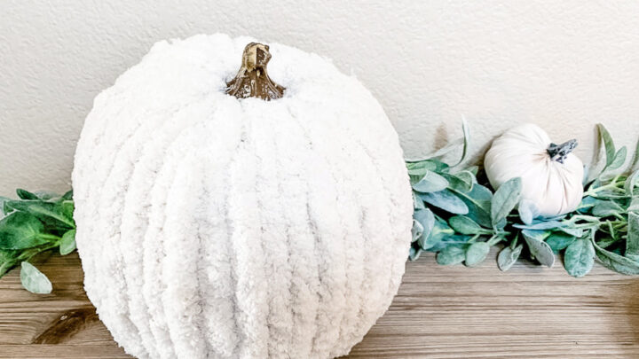 White chunky yarn wrapped pumpkin sitting on a wood table