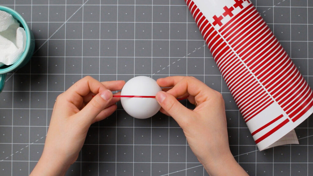 Decorating a white painted ornament with red vinyl stripes