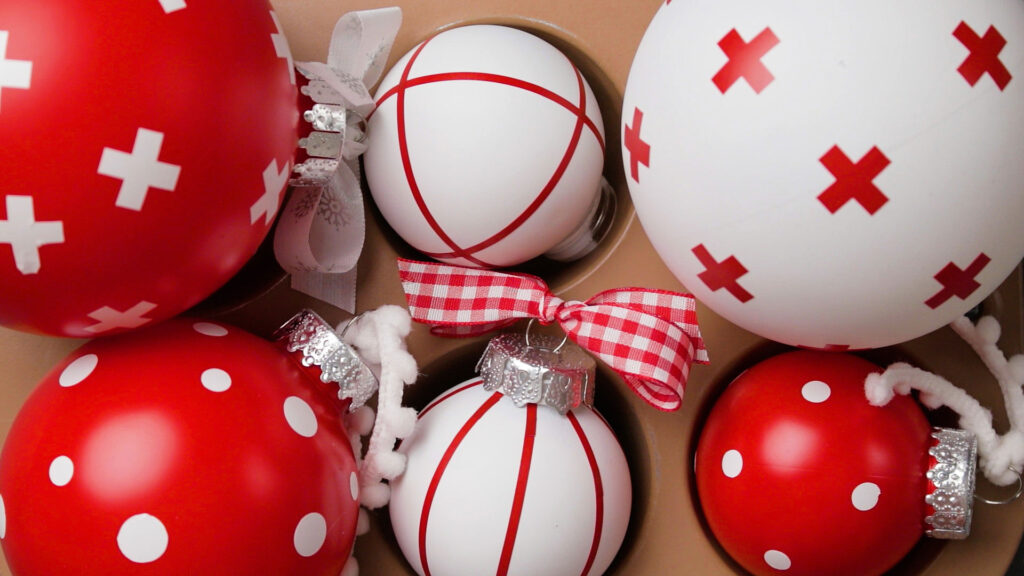 Red and white Christmas Ornaments decorated with vinyl and ribbons sitting in a muffin tin