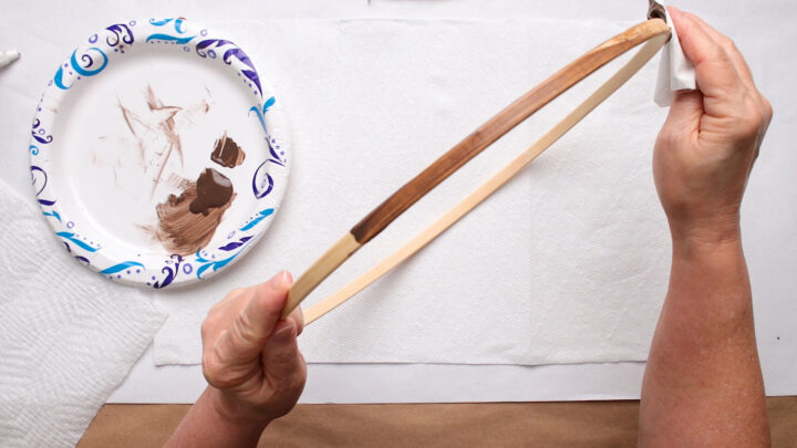 Applying stain to the wooden embroidery hoop with a cloth