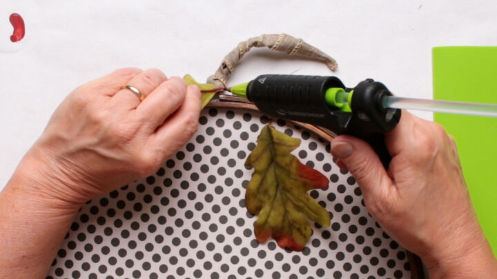 Attaching the leaf to the paper pumpkin with hot glue