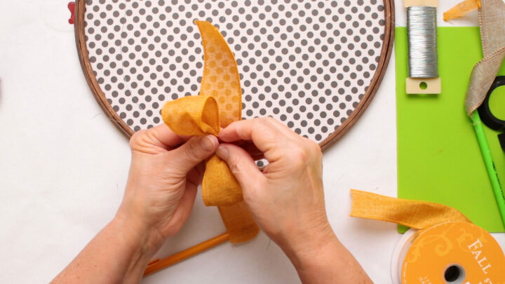 making an orange ribbon bow with one loop for the paper pumpkin