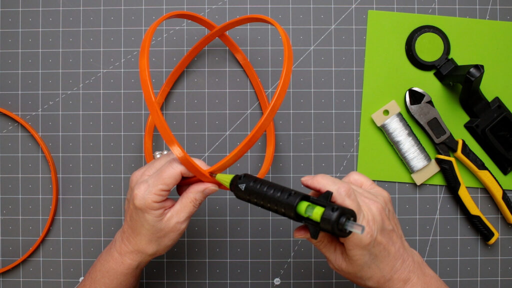Placing hot glue on the bottom center hoops
