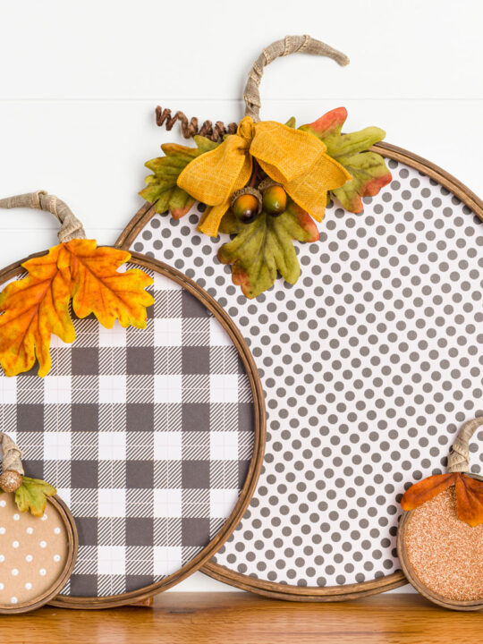 Fun paper and embroidery hoop pumpkins sitting on a fireplace mantel