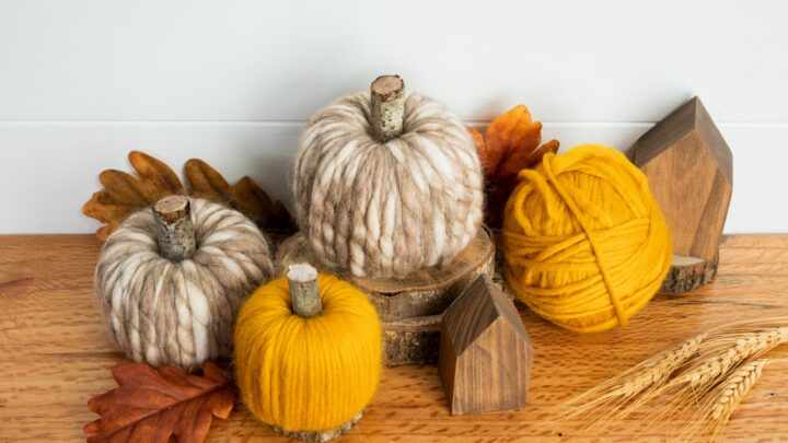 Yarn wrapped Pool noodle pumpkins sitting on a wood table