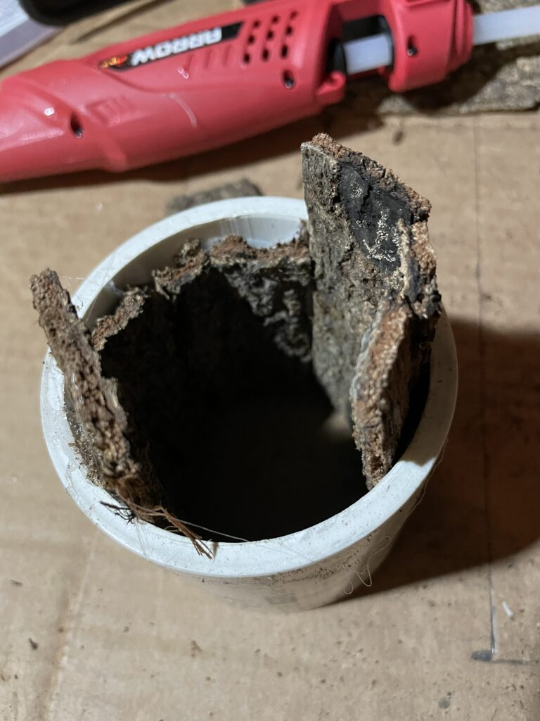 PVC pipe lined with tree bark sitting on a table