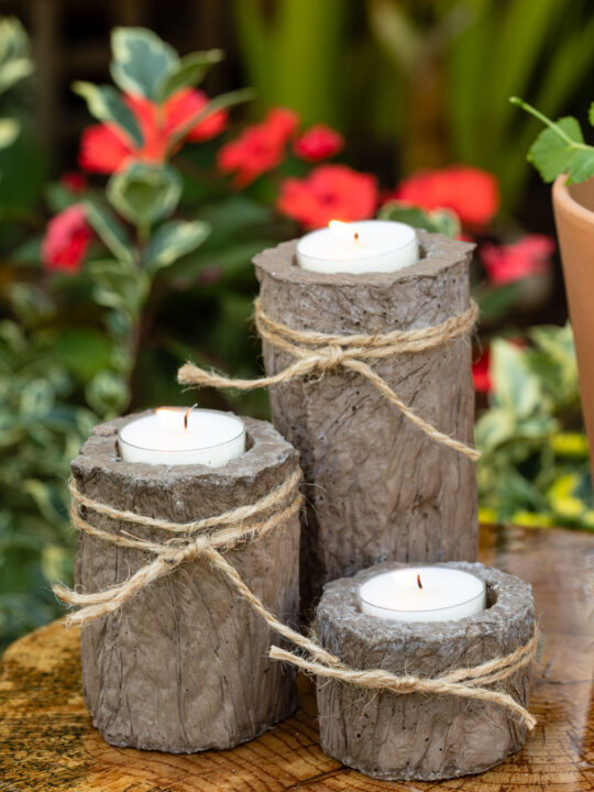 Cement candle holders with twine ties sitting on a wood slice table