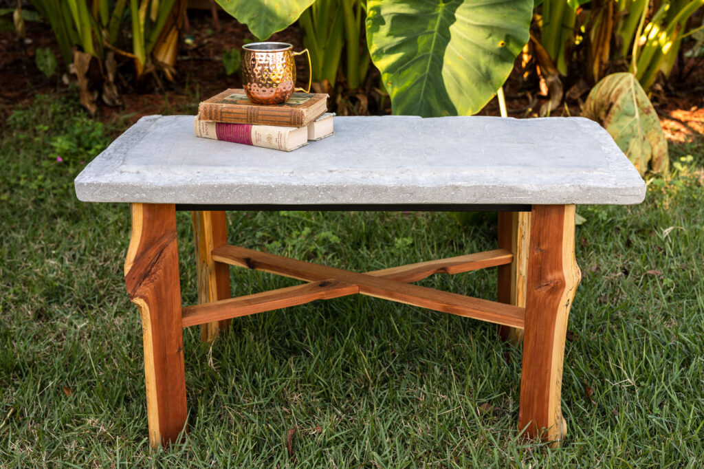 Concrete table top with wood base sitting in the garden with books and a Moscow Mule mug on the top