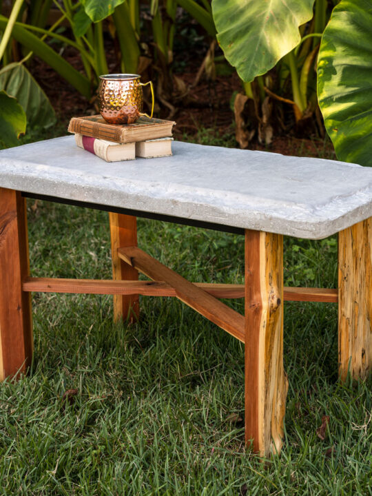 Handmade table with cement top and wood base sitting in the garden